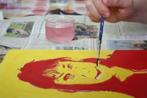 Une personne travaillant son portrait à la peinture.