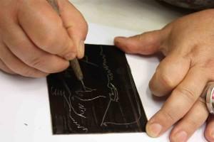 Une personne gravant sa plaque à l'aide d'une pointe ronde.